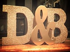 Glitterized wooden initials for our wedding decor: nailed 2 of each thin letters from Michaels together so they would be thick enough to stand. Add modge podge and gold glitter (spray paint for ampersand). Voila!