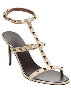 Rock stud sandal in nude from Valentino. This leather sandal features an open toe, T-strap upper with metal pyramid studs, and anklet with an adjustable buckle. Heel measures 3.5