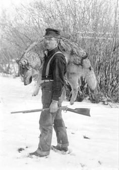 """Coyote Smith with a wolf. Smith was a jack of all trades, working as postmaster, newspaper editor, photographer, trapper, musician and even city marshal. Smith began hunting coyotes with one trap, rifle and hatchet. """"Coyote"""" Smith walked his trap line, harvesting coyotes, wolves, skunks, bobcats and muskrats as well as deer, antelope, grouse and rabbits to keep his family fed. It turned out he had quite the talent for it and hides piled in front of the cabin. From the Wyoming State Archives."""