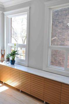 Die moderne Heizkörperverkleidung ist breit gestaltet und besteht aus Holzleisten
