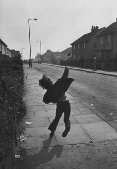 """Gilles Peress     Young Boy Throwing Stones at British Soldiers During """"the Troubles,"""" Belfast, Northern Ireland     1971"""