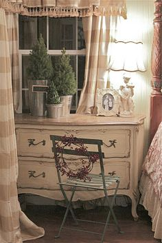 """French Country Cottage: """"One of my bistro chairs came inside to sit near the commode that serves as my nightstand.  It's a perfect spot to stack my latest reading. I love the red berry twig wreath tied to the back."""""""