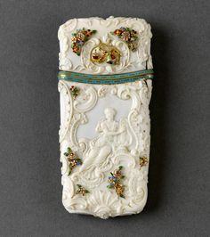 "Carnet de bal | Royal Collection Trust. Rectangular carved ivory carvet de bal [box] mounted with gold and enamelled flowers, leaves, insects and a crowned ""O.N"". Curved rim mounts enamelled turquoise. Carved shells, cartouches and scrolls all over the box, a putto one side, a harp player the other"