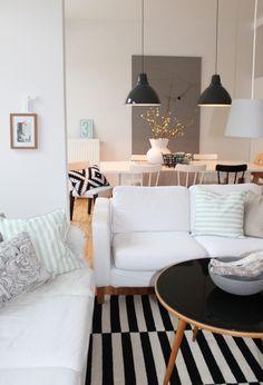 sofá branco na decoração da sala de estar com mesa de centro preta e luminparias pendentes de teto pretas