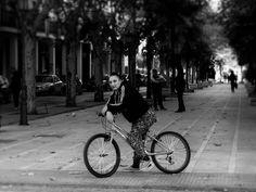 """Une cycliste toute en fucsia vêtue avec son vélo assorti, observe les photographes en haut du Paseo Molino de Viento. D'après la photo de Doisneau """"Congés payés. Byciclette""""."""