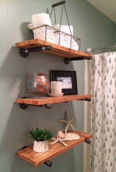 Very cool DIY plumbing pipe & wood bathroom wall shelves. Wall Paint color is Silvermist by Sherwin Williams