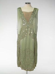 1927 Green satin and bead embroidery.  Sleeveless with low curved neckline in front. Two tongue-shaped satin panels covered with beadwork and lined with silver cloth covering front, and forming shoulder straps. Band of beadwork continuing down bodice back to form V neck filled in with flesh coloured silk crepe, and round low waist to bodice front. Skirt hangs free. Panels very heavily embroidered with beads round edges and at hem.