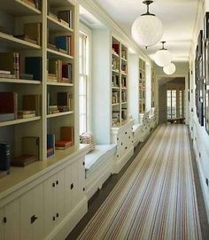 Love the bookshelves and window seats going down the left side of this hallway!