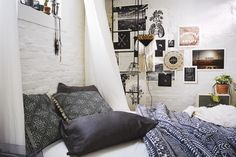 Cool poster collection on white brick walls with soft bedding and white drapes.  Bed feels too low and far from window.