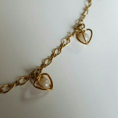 """Avon Hollow Heart Inner Pearl necklace This lovely gold tone Avon necklace has hollow hearts that have two coming together and a white irredescent  color plastic pearl in the center, very cute and classic. 19 1/2"""" long in perfect condition! Great with your favorite shirt and jeans.  Other Avon jewelry is available in my closet. Avon Jewelry Necklaces"""