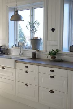 Concrete counter top, white cabinets, subway tile & paneling.