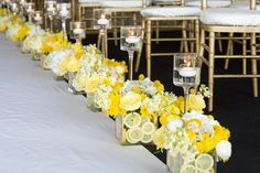 Sunny & Bright Amazing Aisle Wedding Decor Idea..!slices of lemon in vases with arrangements of yellow & white. Every other is a tall candleholder with floating candles. !.. Love