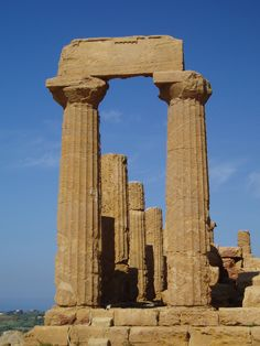 These are ancient Grecian columns of the Doric style. Notice no base at the foot of the column, concave vertical fluting around the entire column, and the minimal ornamentation of the captial. From the capital, the column meets a square piece of stone called an abacus which then connects to the top horizontal stone. This temple dates back to about 580 BC.