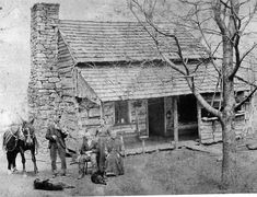 This is a log cabin home in the 1800's . It has a chimney on the side of the home. It also as a very small front porch. This cabin is a very wooden area. This is probably a one room home.