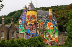 The Earl of Glasgow, Patrick Boyle (CENTRE L), and his son David, the Viscount Kelburn, pose for photographers as they look at graffiti paintings by Brazilian artists on the walls of Kelburn Castle near Largs, Scotland August 30, 2011. Boyle, the owner of the castle, has written to Historic Scotland asking if the mural, which was completed by Brazillian graffiti artists in 2007, can be kept after the three-year time limit, which was put on the artwork by the local council, has expired.