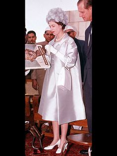 DECKED OUT DOWN UNDERThe Queen returned to Wellington, New Zealand (two years after her visit there had been cut short due to her father's death), in high style. Her shimmering rose gold one-shoulder gown with floral embroidery, plus a striking tiara and white fur, embodied regal glamour.