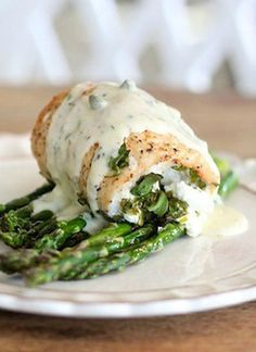 Yummy spinach and goat cheese stuffed chicken with asparagus and cream sauce. So easy I'm trying this for dinner tonight