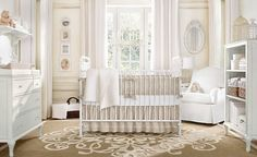 This neutral toned nursery in beige and white centers around leaf-detail rug, with all-white furnigure including shelving and dresser, with corner slipcover armchair under oval wall mirror.