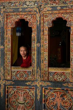 Bound for Bhutan | A Buddhist monk looking out a window of his monastery in Bhutan √