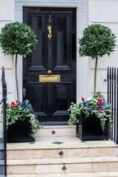Black door, inlaid limestone steps, bay tree topiaries with flower underplantings