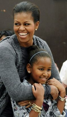 Michelle Obama smiles broadly as she is greeted by volunteers singing Happy Birthday to her at Stuart-Hobson Middle School in Washington...age 11
