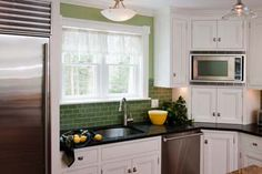 This is the set up I like! Microwave conveniently tucked in angled corner cabinetry, and an appliance cabinet under the microwave with a small cabinet above.