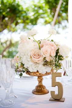The guestbook table will feature a gold compote vase filled with cream hydrangeas, blush garden roses, pale green succulents, blush spray roses, and grey dusty miller  www.stemfloral.com | www.jennydemarco.com |  www.villadellagoevents.com