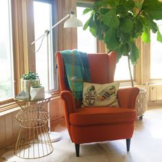 The bright red wingback chair in the reading nook of this Cleveland home mixes a classic shape with modern legs.