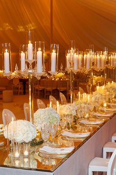 A mirrored table is lined with vases of white blooms and lucite candelabras.