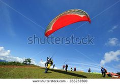 Ranau Sabah Malaysia - May 18, 2014:Unidentified paraglider prepare to take-off at Sonsoluyon paragliding spot.This spot is popular with scenic view with Mount Kinabalu as an major attraction. - stock photo