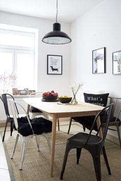 Man nehme helles Holz und cooles Metall, mische es mit Schwarz-Weiß und einer Prise Farbtupfern – herauskommt das beste Rezept für eine moderne Küche im Skandi-Look! Sobald sich die Sitzecke durch einen Teppich zum Rest des Raumes abgrenzt, wirkt sie gleich viel wohnlicher. Steht der Esstisch in der Küche, empfehlen wir einen Sisal-Teppich. Der ist absolut pflegeleicht und schmutzabweisend. Und fügt sich wunderbar in den Gesamtlook ein, weil er farblich mit dem Holztisch harmoniert.