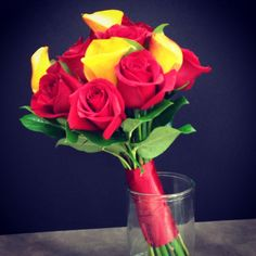 Red and Yellow Bride Bq. Red roses with mini flame calla lilies and some salal leaves around edge to finish it off. Wrapped in red satin.