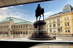 Vienna, Austria. Photo: People sit near the Statue of Duke Albrecht in Vienna, Austria.