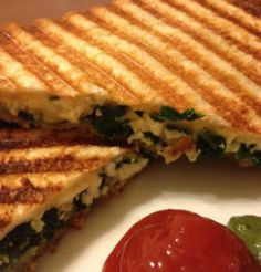Spinach Paneer Sandwich Spinach – 1/2 cup, chopped Paneer – 4 slices Tomato – 1, small, sliced Red Onion – 1/8 cup, finely sliced Bread Slices – 4 Garam Masala Powder – 1/4 tsp Onion – 1/2, chopped Red Chillies – 1, small, seeded, finely chopped Garlic – 1 to 2 cloves, chopped Ginger – 1/2 tsp, grated Plain Yogurt – 1 tblsp Lettuce Leaves – handful Salt as per taste Pepper Powder as per taste Olive Oil – 1/2 tblsp