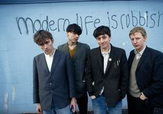 The four members of Blur, Damon Albarn with left, portrayed in 1994 before a painted with the name of their second album.