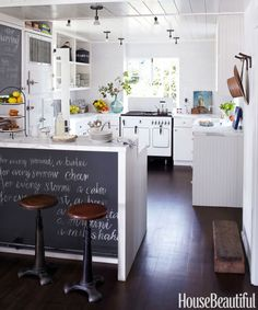 In a Marin County, California, beach house designed by Kim Dempster and Erin Martin, the blackboard on the breakfast bar is an opportunity for an intriguing quote. Subway tiles by Heath Ceramics remind Dempster of the inside of a shell. Gemini ceiling lights from Alfa. Paint throughout the house is Benjamin Moore's Snow on the Mountain.