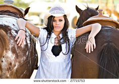 A young woman poses with two saddled horses