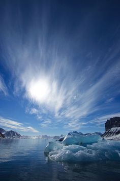 Blue ice under a blue sky with streaky clouds.