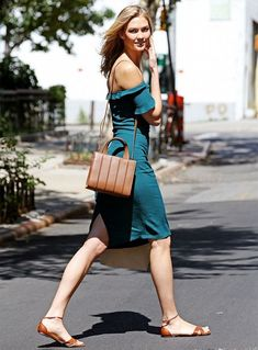 Karlie Kloss wears an off the shoulder teal fitted dress with a brown crossbody bag and black sandals.