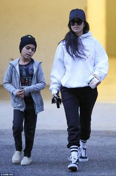 Keeping cool:Along with the on-trend outerwear she wore a pair of black sweatpants that were tucked into a pair of white striped socks along with black Vans Old Skool low-tops