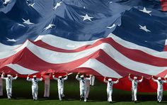 San Diego, CA: US sailors unroll a giant Stars and Stripes before a baseball game. (Photograph: Denis Poroy/Reuters)