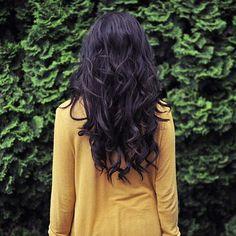 long black hair, golden shirt, and greenery.