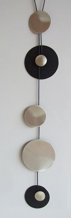"Pendant ""Silver Cercle"" by Estela Guitart.Long silver pendant with Urushi Japanese lacquer, tribute to Calder. Silver circles are suspended and accompany the movement of the body. When they spin the sequence changes, revealing another different surface finished with the same care."