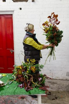 One of the students is creating a front facing bouquet at our winter hand tie workshop . Edinburgh / florist / chrysanthemum / kangaroo paw / contorted willow /