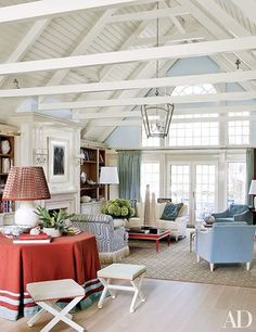 In the living area of Christopher Burch's getaway in Southampton, New York, a lantern from Circa Lighting hangs above a cocktail table and blue armchairs from Burch's forthcoming furniture line for No. 9 Christopher; the scroll-back armchair is covered in a Raoul Textiles print | archdigest.com