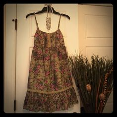 Gorgeous Olive Green Dress w/ Floral Pattern Like new! Worn 1 time. Very vintage looking combo of olive green color variations & olive lace with purple/pink & teal flowers. 3 small wooden buttons detail the top front. Adjustable spaghetti straps and stretchy elastic back section to help fit a range of sizes. Size M. Fits up to at least a 34D/36C, probably could go a little bigger on top. More beautiful in person! Maurices Dresses