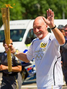 Carrying the Olympic Torch through the Croydon district of London on July  23, 2012.