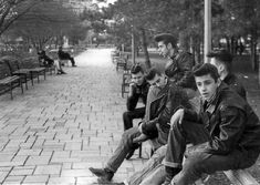 American greasers hang out in the park. The greaser subculture began in the 1950s with the advent of rock and roll and era was comprised largely of rebellious, working-class youths obsessed with hot rods and music. The name greaser came from their greased-back hairstyle, which involved combing back hair with, wax, tonics or pomade.
