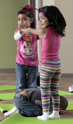 "Melissa Valdez, (left) and Adilene Soto make a bridge as Leo Alvarez poses as an ""egg"" while Angela Moorad teaches yoga to three and four-ye..."