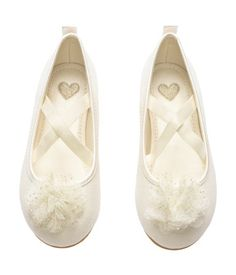 Ivory ballet flats with crossed elastic straps over foot. Rubber soles.